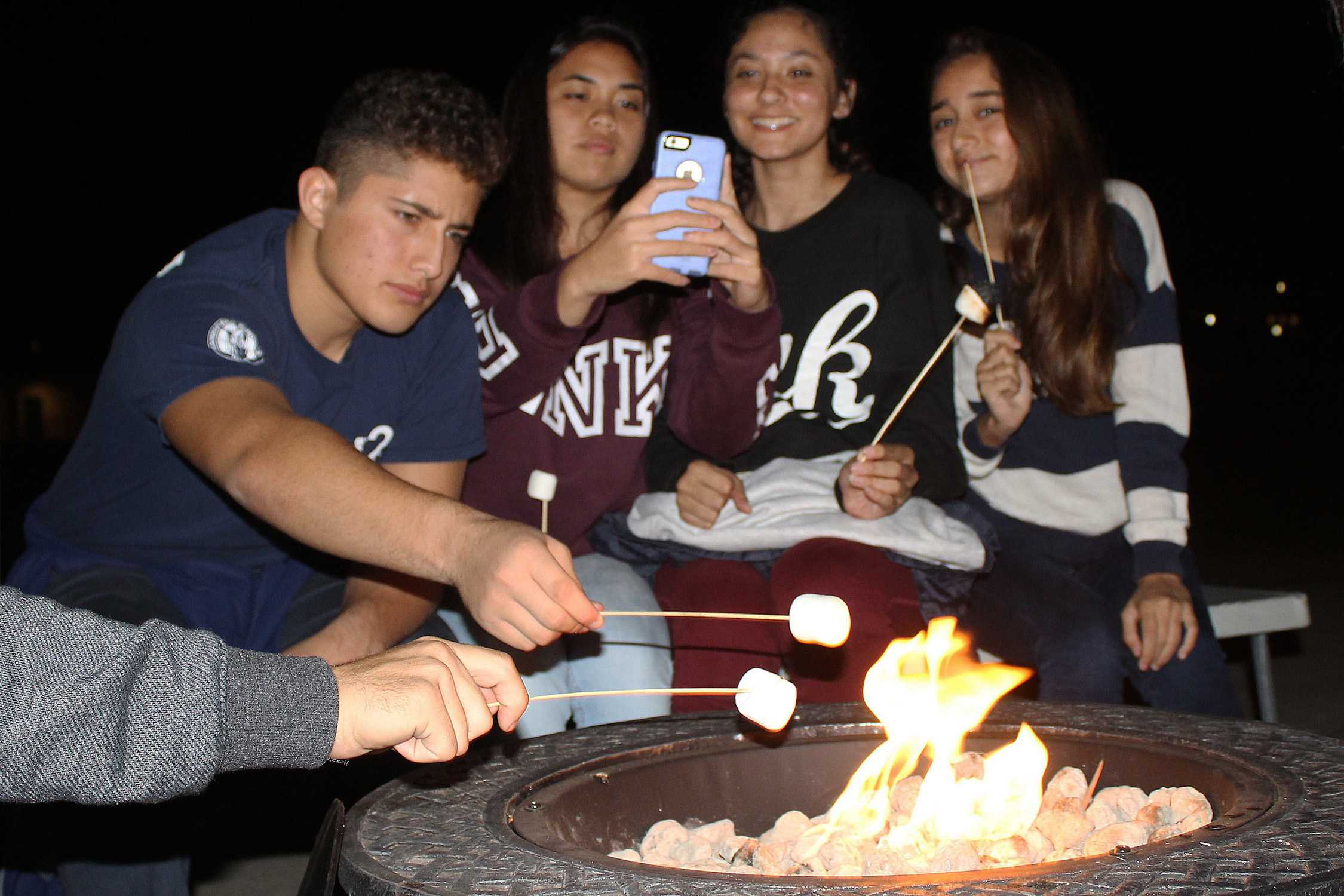 Sophomores gather around a fire pit roasting marshmallows for s'mores. Instead of sleeping over, sophomores spent an early night bonding with their class and their family.