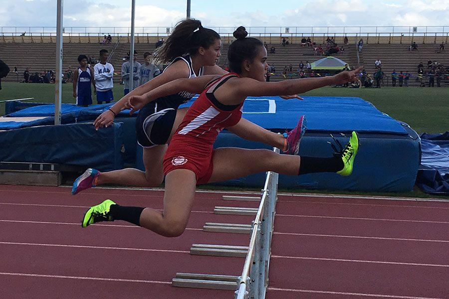Freshman Kahiau Bonacarsi leaps over a hurdle on her way to finishing 3rd in the girls 100-meter high hurdles. The first meet of the 2016-2017 MIL season took place yesterday afternoon at War Memorial Stadium. Many new and old athletes competed and cheered as they watched their fellow teammates compete as well.