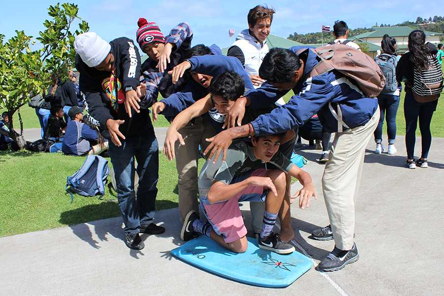 Juniors form a barrel over Kahiau Luat-Hueu who is dressed as a bodyboarder on Tuesday, Sports Day. Spirit week was filled with many dress-up days.