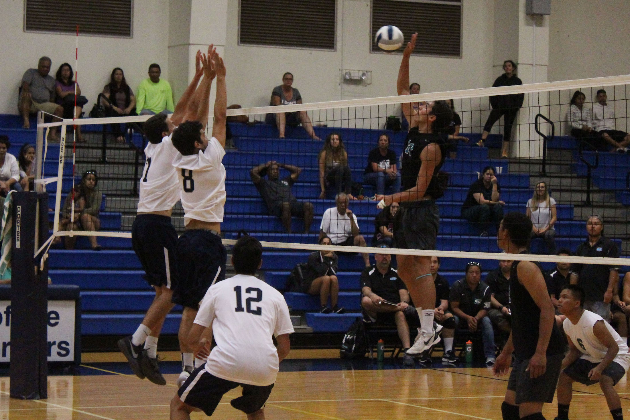 Seniors Hanalei Hoopai-Sylva and Keahi Jacintho jump for a block against Nā Aliʻi. The Warriors got their first win in four years against Nā Aliʻi, Saturday, April 15, at their home gym.