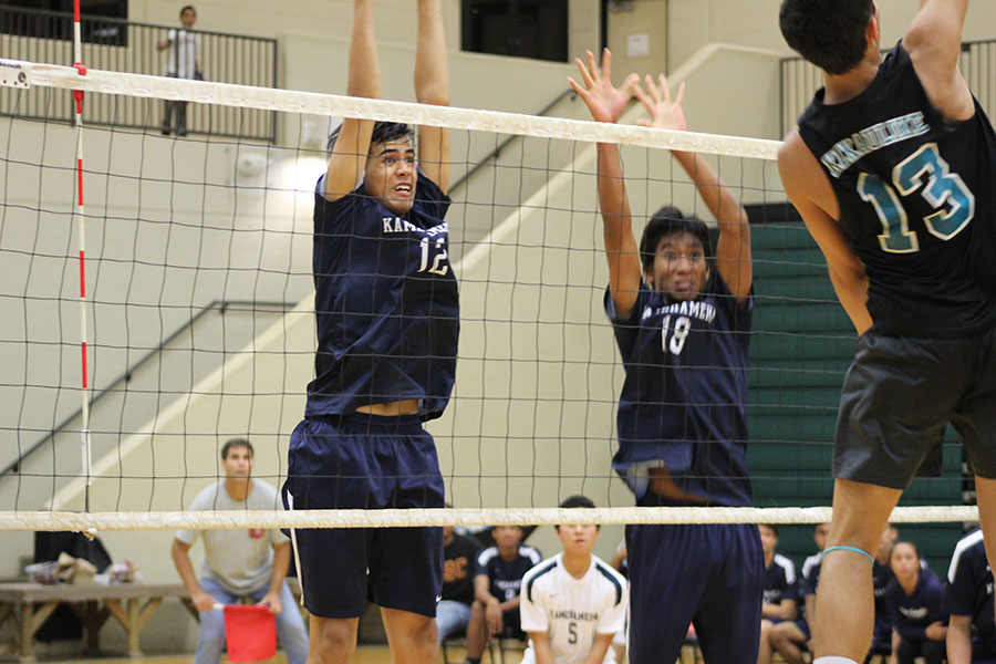 Senior Hāweo Johnson and junior Rafael Adolpho jump to block a King Kekaulike hitter in their last MIL season game, Thursday, April 20. The bleachers at King Kekaulike gymnasium were full with supporters for both schools. Nā Aliʻi came out with the win to end their season 11-1, and the Warriors finished 9-3