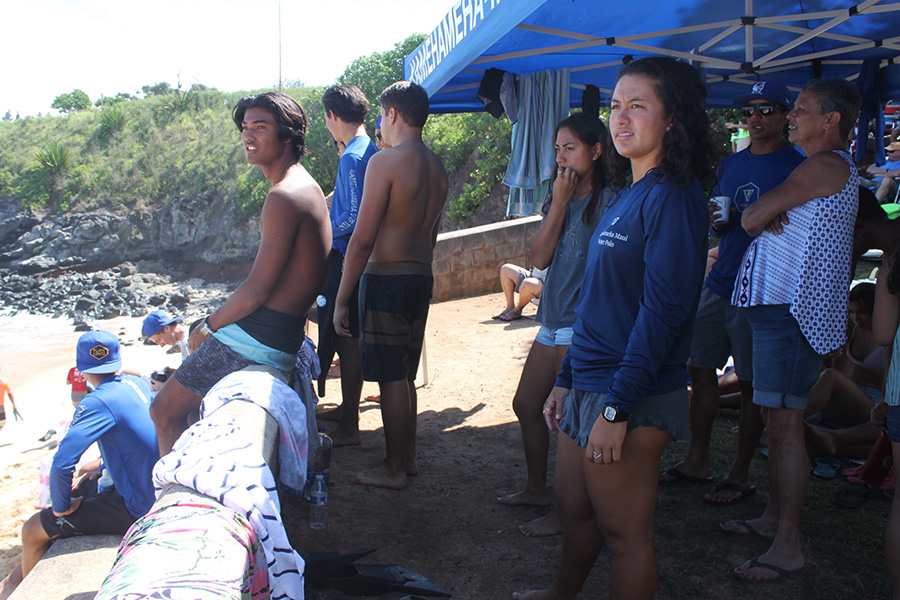 The+surf+team+looks+out+to+the+ocean+watching+for+their+teammates+to+catch+a+wave.