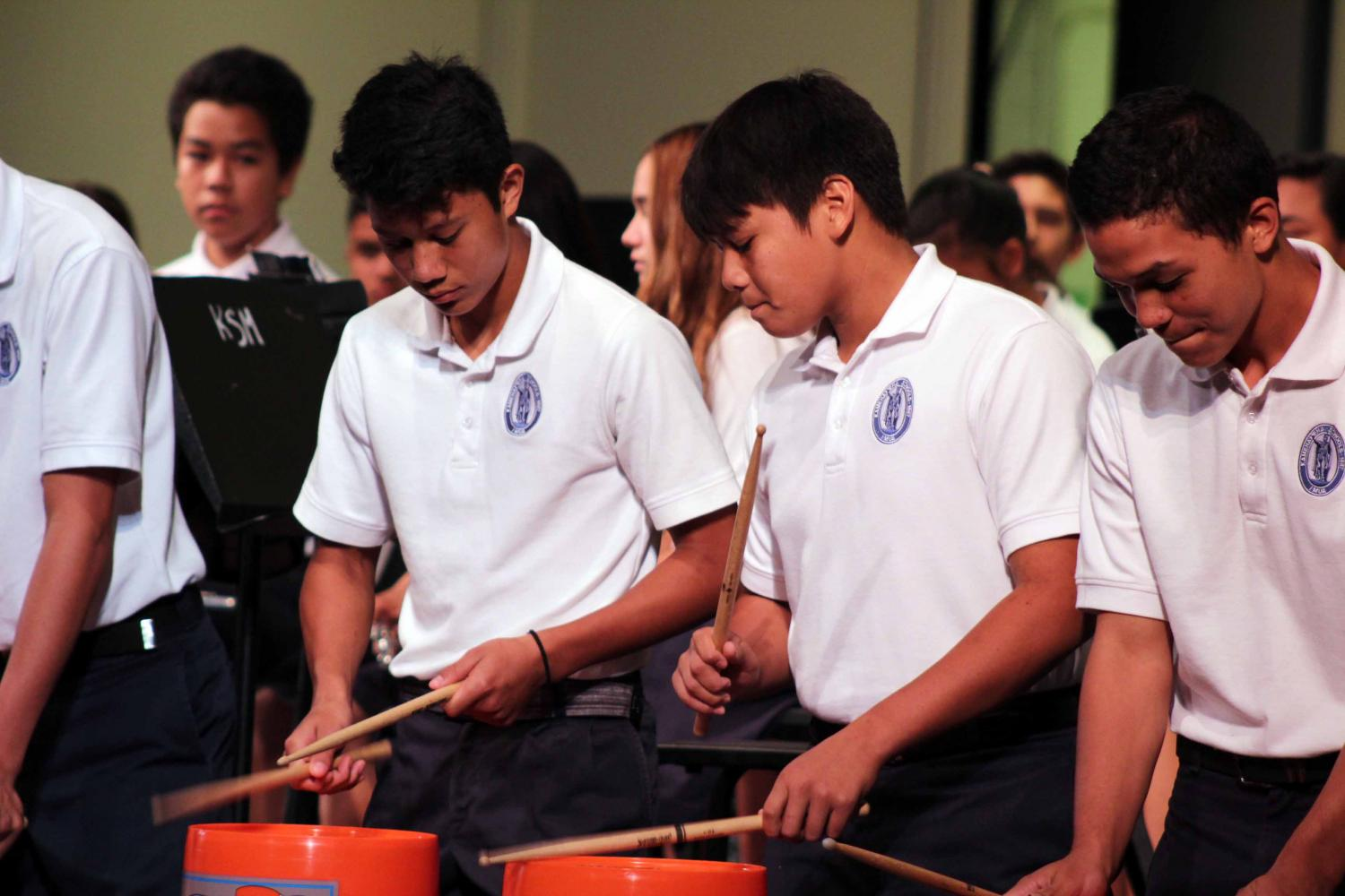 Eighth+grade+percussion+band+members+kneel+in+front+of+the+audience+and+perform+using+buckets.
