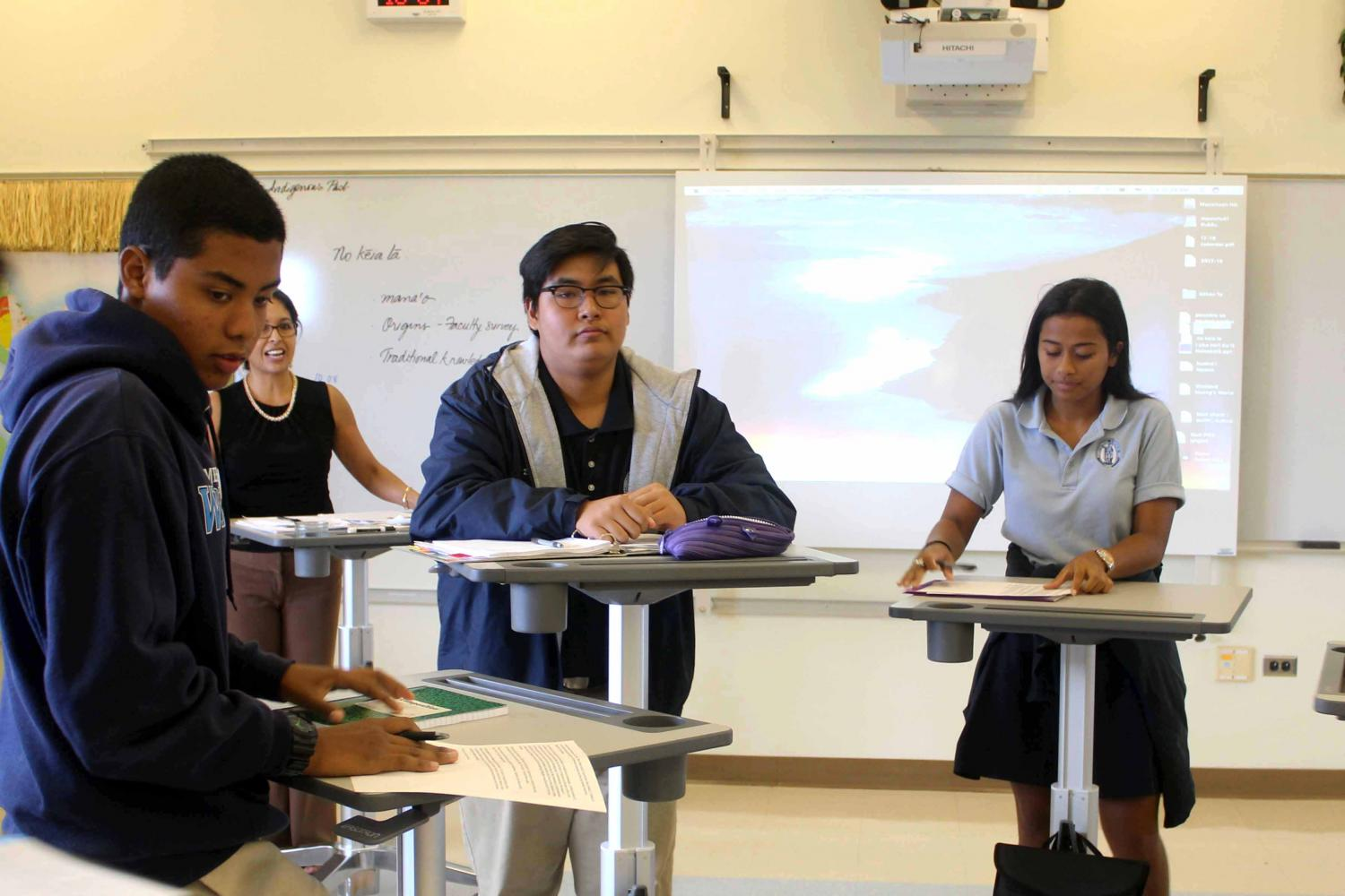 Seniors Kaleo Deguilmo, Dylan Falces, and Delissa Rano listen while Kumu Kapulani gives instructions. Kumu Kapulani converted her traditional desks with chairs to standing desks to improve brain and body engagement in her classes.