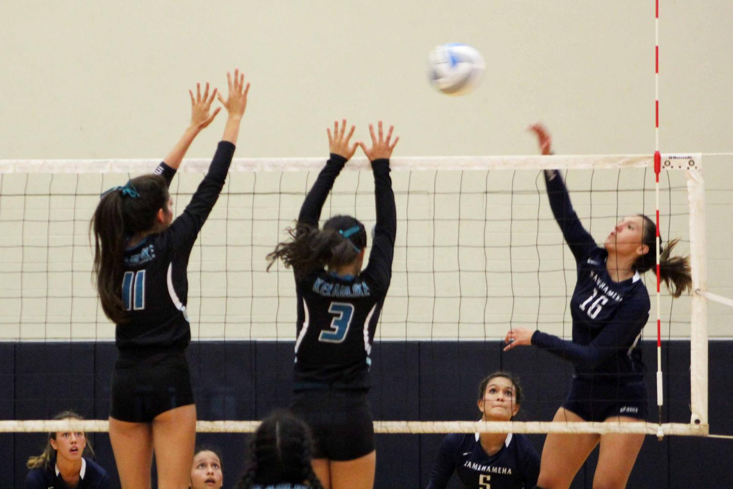 Kamehameha Maui junior Alea Cervantes hits the ball past Nā Aliʻi blockers. Warriors defeated Nā Aliʻi in girls volleyball, 3-1, at King Kekaulikeʻs gymnasium. Aug. 29.