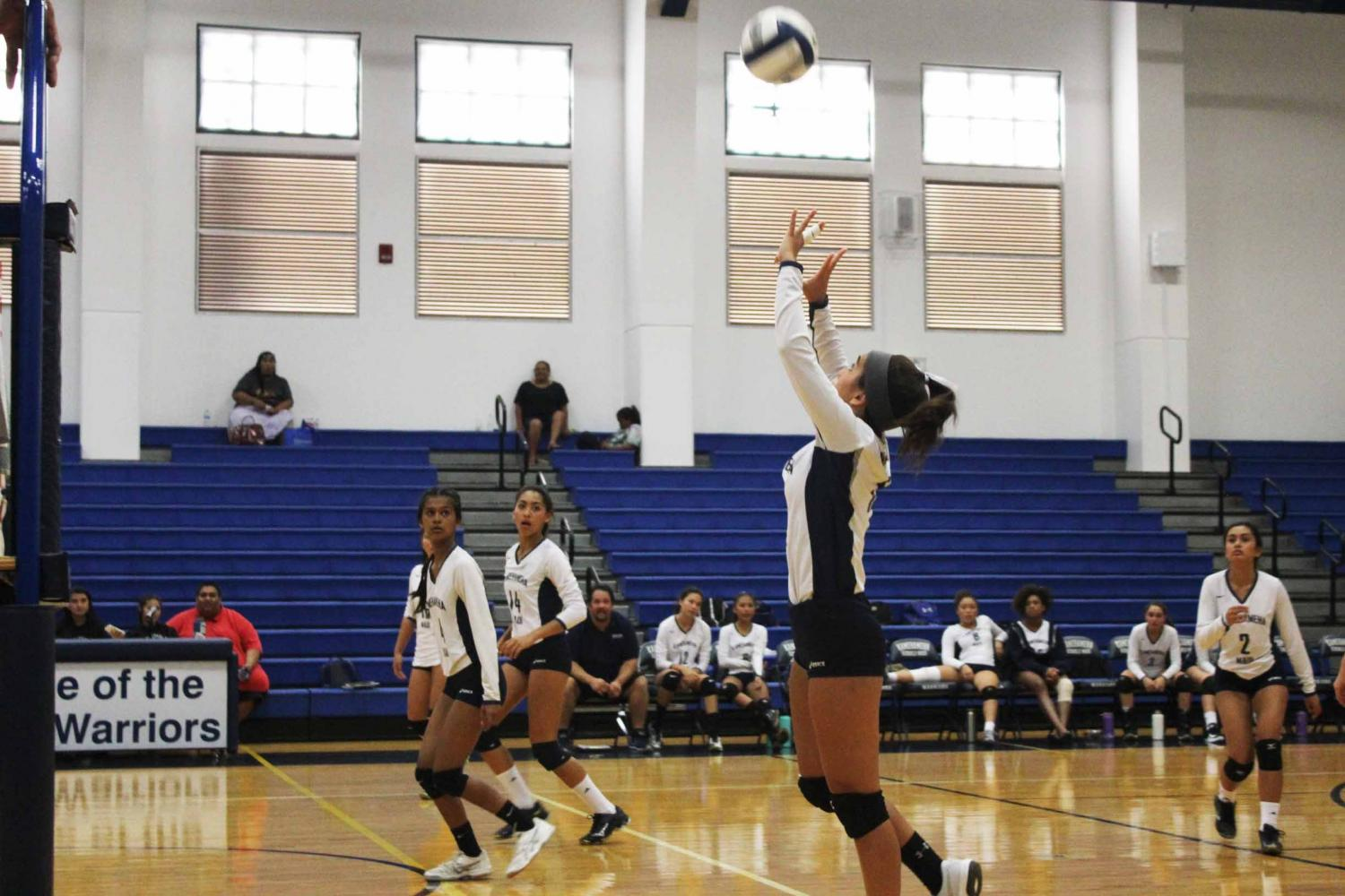 Freshman Laʻakeaokalani Awai sets the ball over the net. The jv girls volleyball Warriors won 2-1 over Maui High on Sept. 28 at Kaʻulaheanuiokamoku Gymnasium.