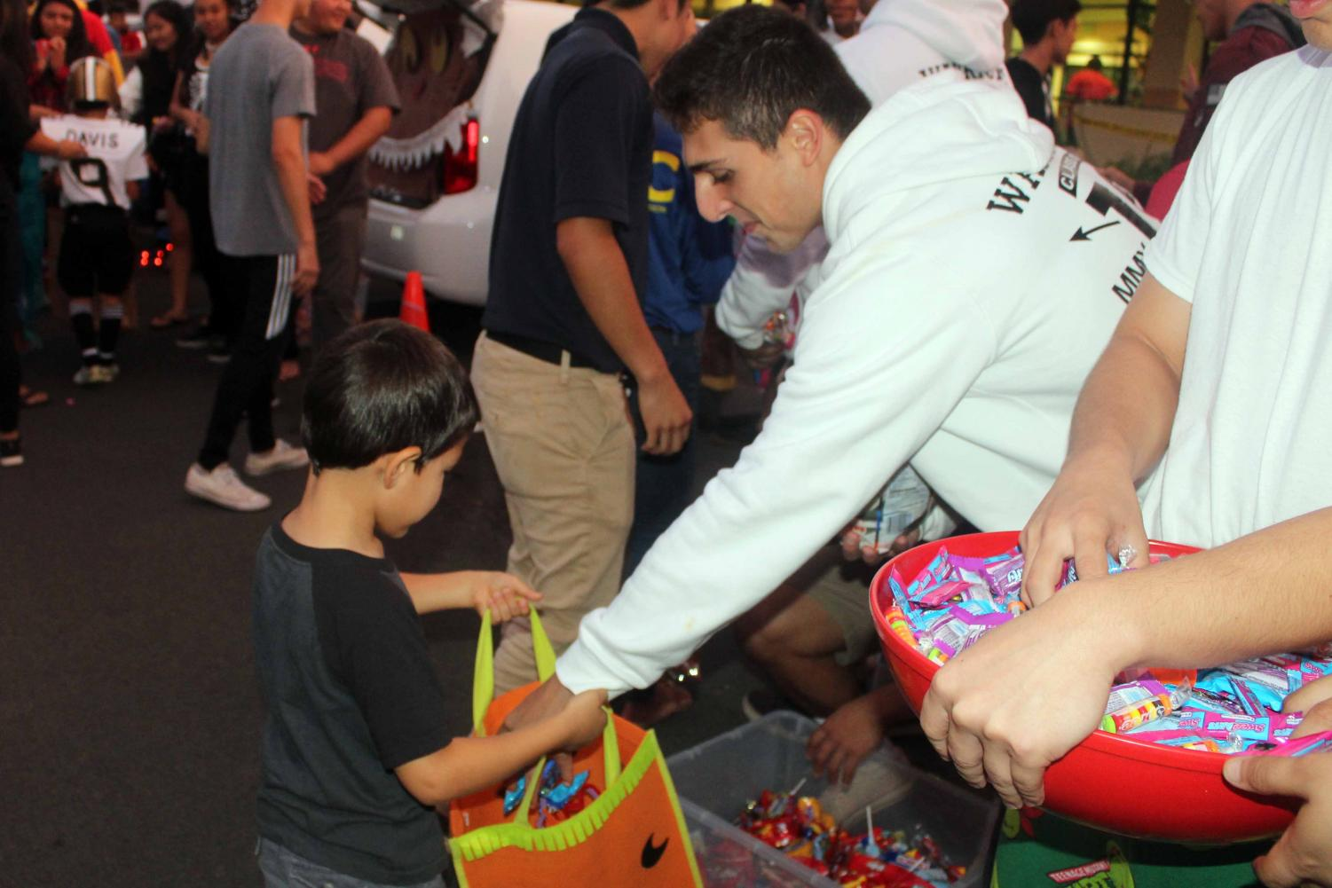 Senior Daniel Kapua gives out candy on behalf of the Letterman's Club. Kula haʻahaʻa returned for a second year of Trunk or Treat at the upper elementary school parking lot, Friday, Oct. 27.