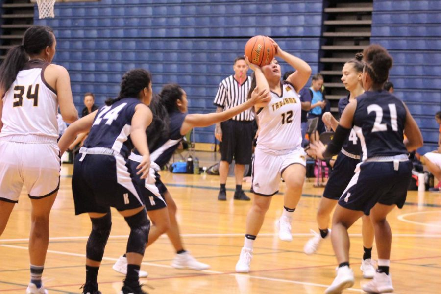 The Warriors work together to block Mililani. The Trojan girls basketball team won 46-42 against the Warriors, Nov. 24, at War Memorial Gymnasium.