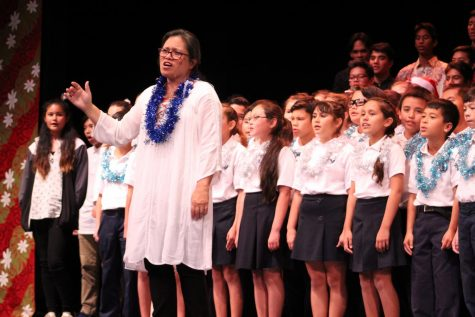 "Mrs. Nitta conducts the audience for ""Pō Laʻi Ē,"" the last song of the night. The Christmas concert brought joy with the performances for both the haumāna and the audience."