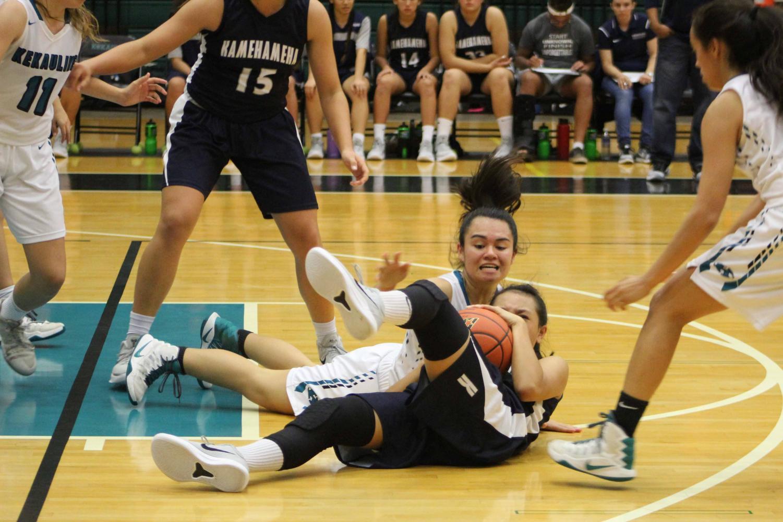 Sophomore Tatiana Soon fights for the ball while King Kekaulike's Liane Tomita reaches for it. The Warriors girls basketball team won, 55-53, against King Kekaulike, Dec. 27.