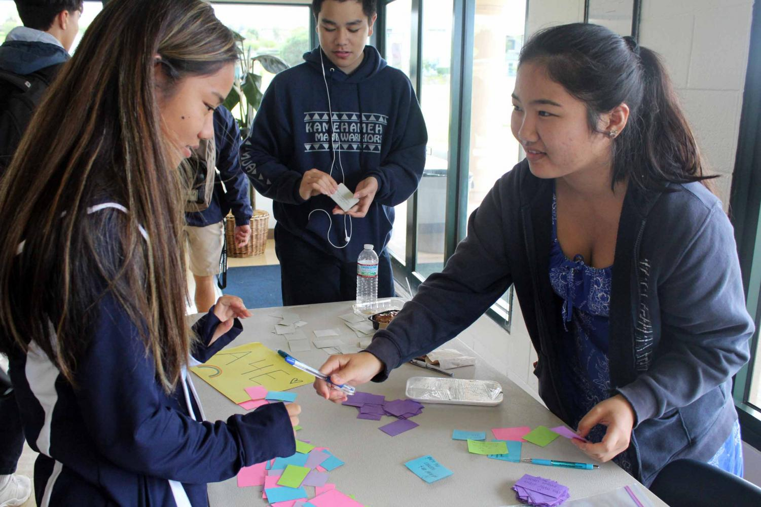 Allies for Equality president Sherri Nagamine hands a compliment to senior Kennedy-Kainoa Tamashiro. Nagamine and A4E honored National Compliment Day by handing out compliments to students in the dining hall, Jan. 24.