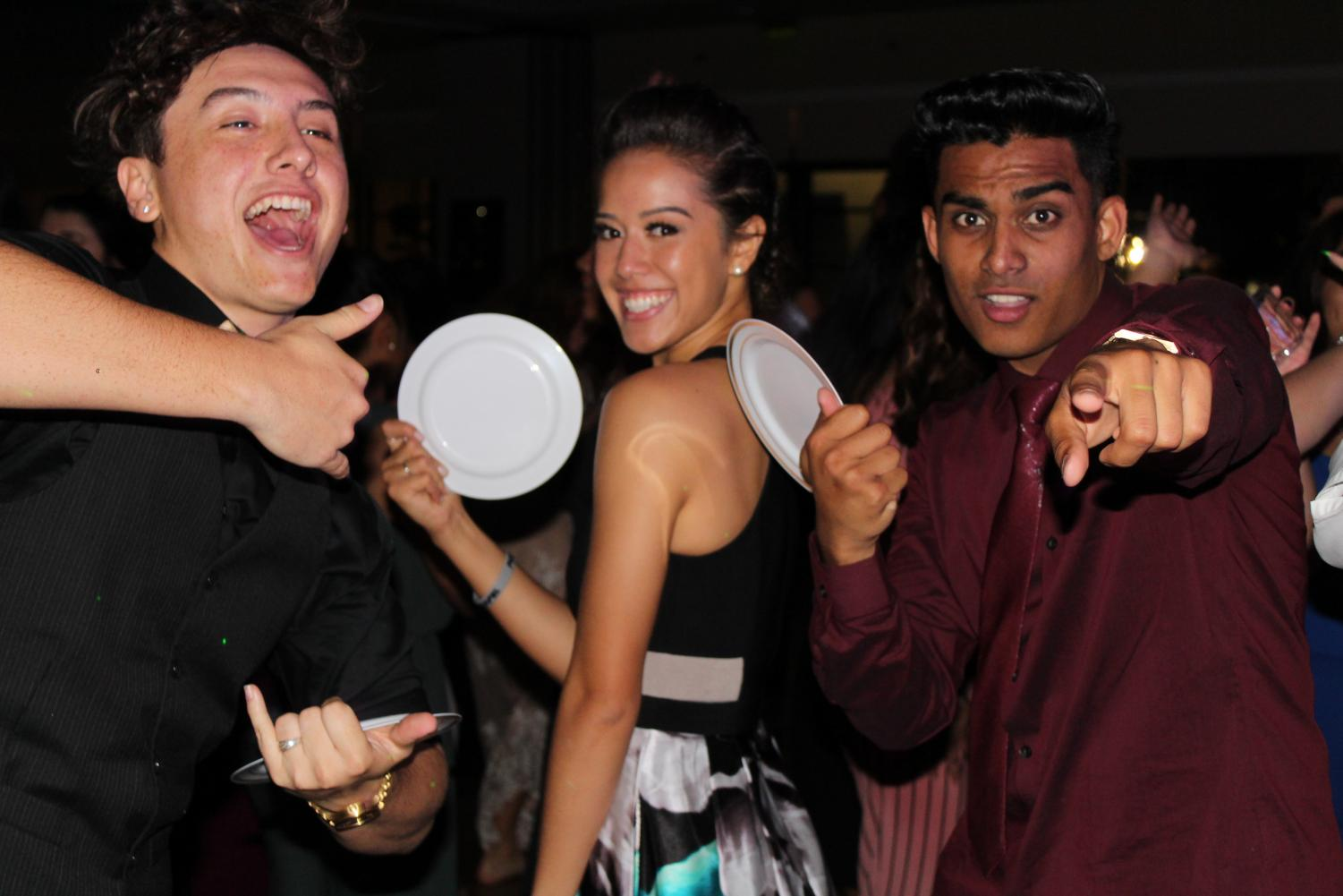 Quinn Warrington, Talia Leauanae, and Michael Singh turn their salad plates into fans as they dance their night away. Ka Papa Lama's senior ball was the school's first masquerade in several years and left students partying in the most glamorous way.