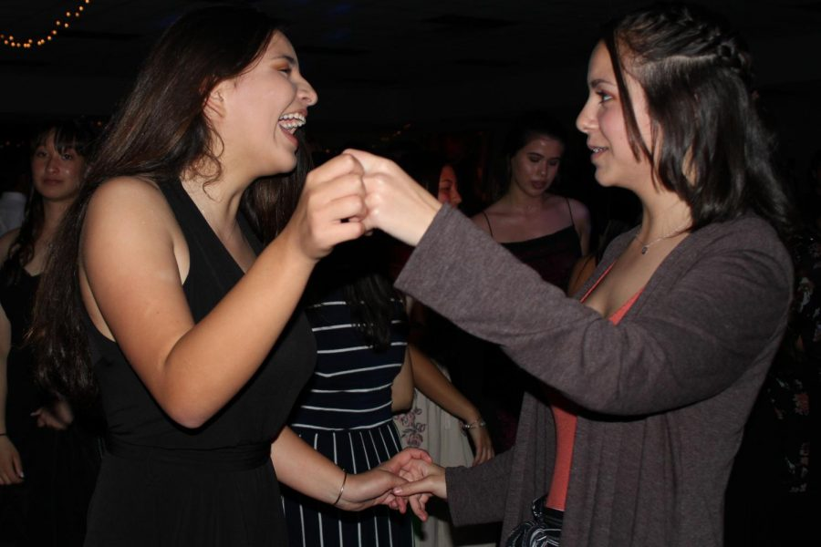 Ali Tavares and Madeline Sylvester laugh with one another while dancing. The freshmen had a 'great' night, Feb. 10, partying like they did in