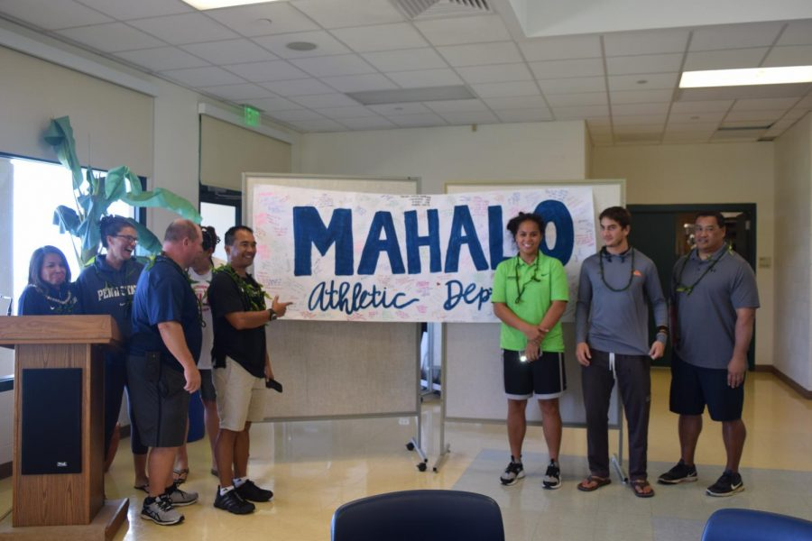 Coaches Dayle Hoopii, Erin Harkleroad, Charles Roggow, Alika Asing, David DeJetley, and Jon Viela, athletic director, stand in front of a sign the Lettermenʻs club put together to celebrate the athletic department March 15. The students gathered at lunch and thanked the athletic department for all they do.