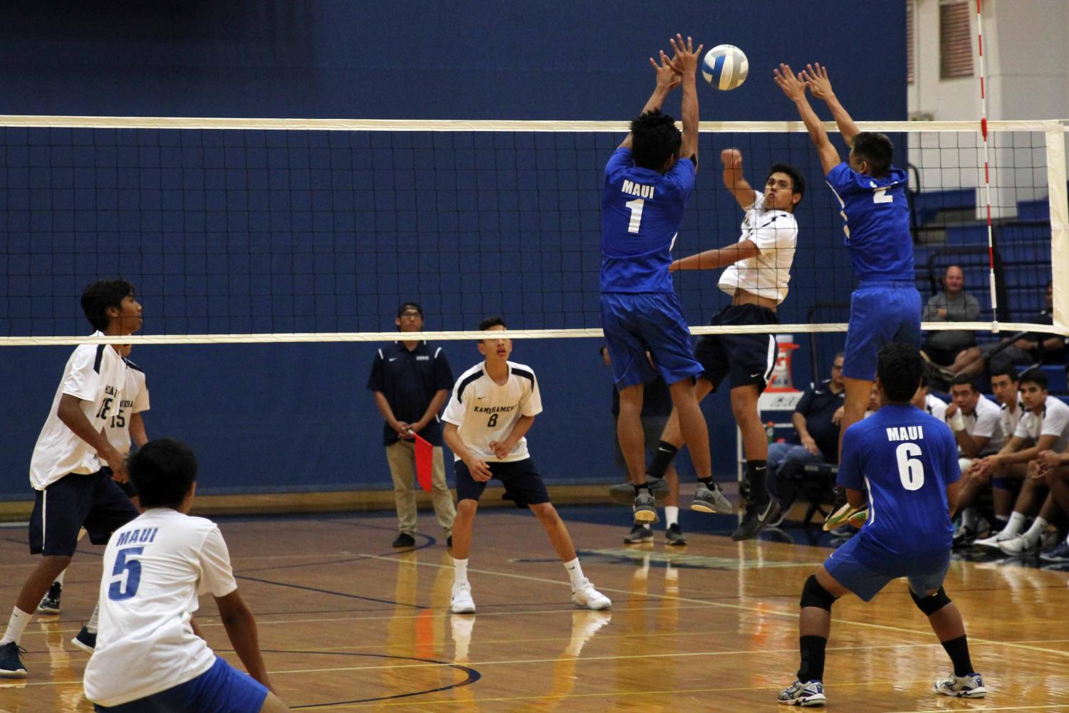 Senior Hinano Long hits the ball past junior Julius Benavidez and senior Rexie Butihi. The Warriors defeated Maui High, 3-0, at Kaʻulaheanuiokamoku Gymnasium Tuesday at 6 p.m.