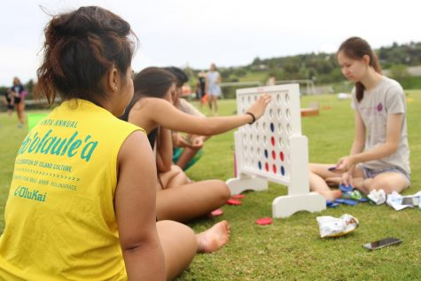 Meaaloha McCabe watches Kela Kauhaʻahaʻa and Melinda Lee play Connect Four.