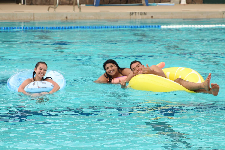 Jaelynn+Nobriga%2C+Cierra+Benson%2C+and+Tyson+Haupu+float+around+the+pool+with+their+floats.