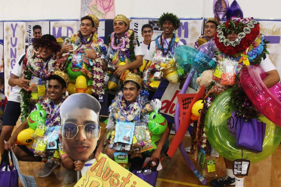 The+seniors+smile+for+a+picture+after+receiving+leis+from+family+and+friends+after+the+game.+