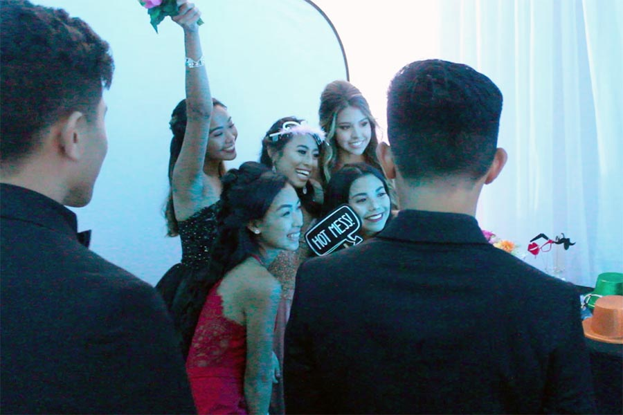 Junior+Duke+Kubota+presses+the+screen+of+the+photo+booth+while+the+girls+ready+their+poses.