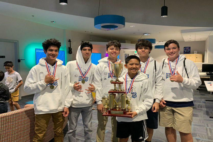 Isaiah+Auweloa%2C+Elijah+Auweloa%2C+Jonah+Walker%2C+Jayden+Walker%2C+and+La%27akea+Goliz+gather+around+Brenden+Hanada%2C+who+is+holding+their+championship+trophy+in+the+Hawai%27i+Esports+Arena.+The+KS+Maui+%27Rocket+League%27+team+won+first+place+in+one+of+three+gaming+championships+held+January+25+at+the+Aloha+Tower.