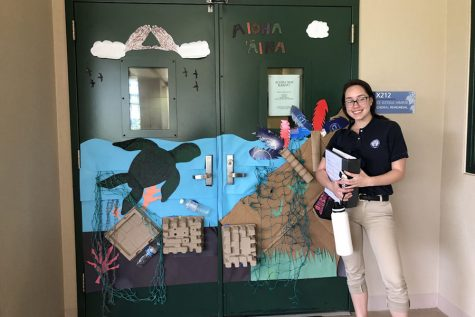 Teilana Akre stands next to her advisory classʻs contest-winning door. Classes were encouraged to recycle and use ʻŌlelo Hawaiʻi to exemplify the theme Aloha ʻĀina for Hawaiian Language Month.