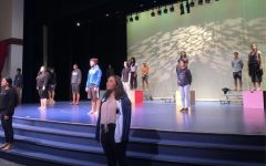 Hawaiian Ensemble practices singing ten feet apart by spreading out on the stage. Some students are placed on risers and boxes to increase the distance and to be seen.