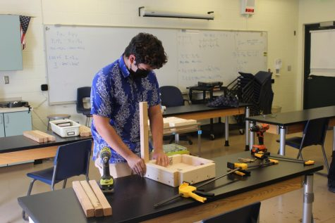 After the school day has ended, Makana Eckel goes to Mr. Lopez's classroom to assemble the wooden pieces to create the stool.