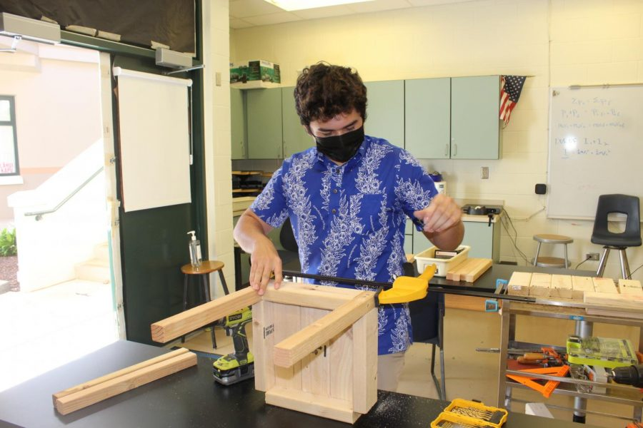 Makananoheamaikalani Eckel puts together a wooden stool to provide portable seating to assist with social distancing, especially at lunch.